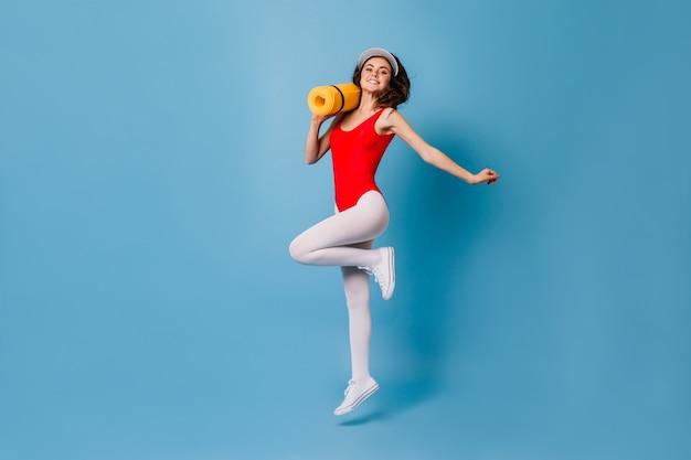 Vrouw in krappe plekken pak springt vrolijk op blauwe muur