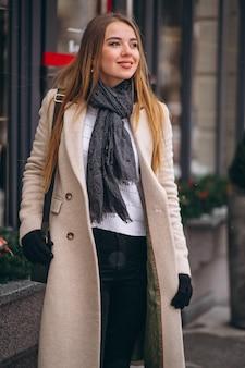 Vrouw in laag die zich buiten de koffie in een de winterstraat bevindt