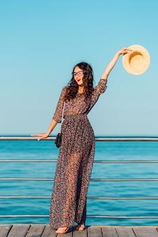 Vrouw in lange jurk en strooien hoed met plezier aan zee