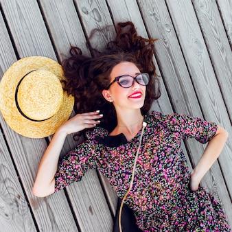 Vrouw in lange kleurrijke jurk en strooien hoed liggend op de houten vloer opleggen