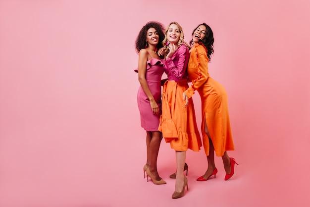 Vrouw in lange oranje jurk tijd doorbrengen met vrienden