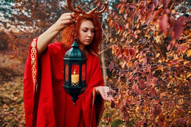 Vrouw in lange rode kleding met hertenhoornen in de herfstbos.