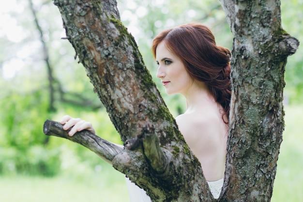 Vrouw in lange witte jurk in zomertuin