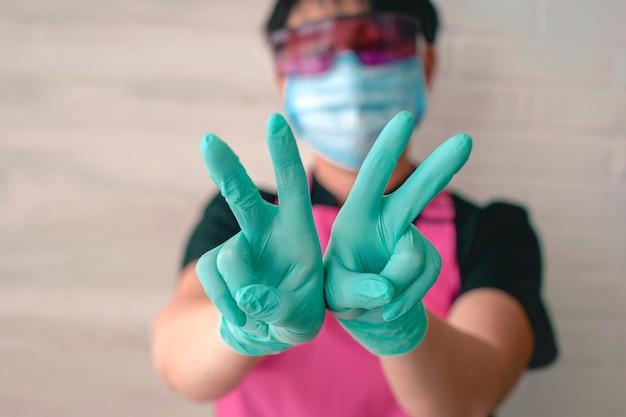 Vrouw in latex handschoenen en roze schort hand in hand omhoog als een overwinningssymbool ok hoop win medisch