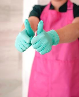 Vrouw in latex handschoenen en roze schort met duimen omhoog als een hoopsymbool ok hoop win concept