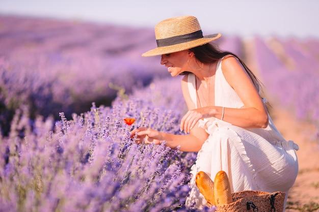 Vrouw in lavendel bloemen veld bij zonsondergang in witte jurk en hoed