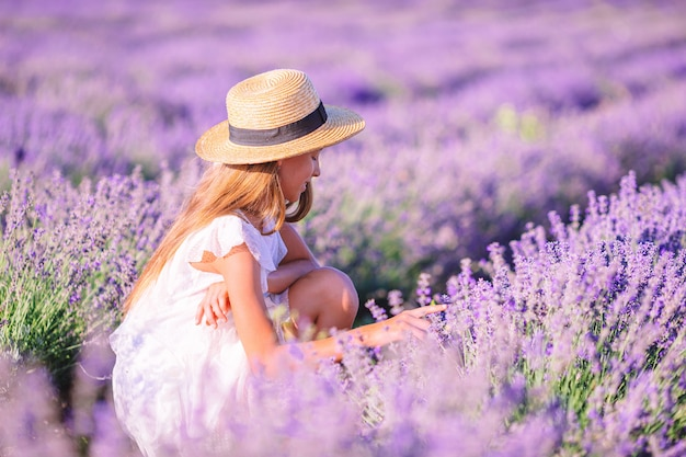 Vrouw in lavendel bloemen veld in witte jurk en hoed