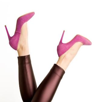 Vrouw in lederen broek en roze hoge hakken schoenen op een witte achtergrond. - afbeelding