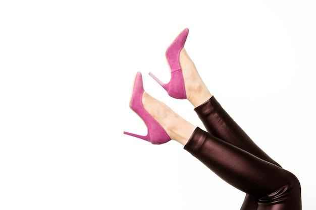 Vrouw in lederen broek en roze hoge hakken schoenen op wit