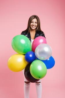 Vrouw in lederen jas poseren met bos van gekleurde ballonnen