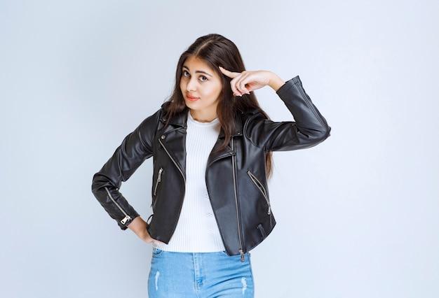 Vrouw in leren jas wijzend naar hoofd en denken.