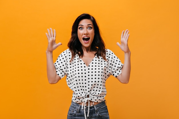 Vrouw in lichte blouse schreeuwt gelukkig en kijkt naar de camera op een oranje achtergrond. prachtig volwassen meisje in polka dot shirt en spijkerbroek is zeer verrast.