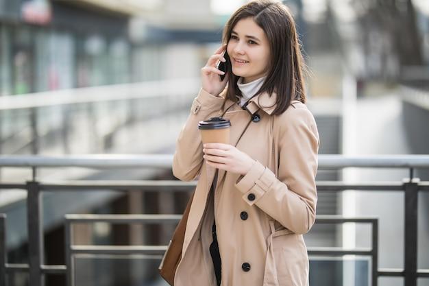 Vrouw in lichte jas lopen op straat en praten over de telefoon