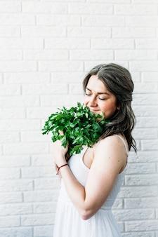 Vrouw in lichte jurk houdt peterselie, kruiden en planten