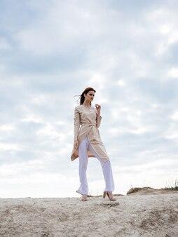 Vrouw in lichte kleren buitenshuis wolken blauwe hemel zand