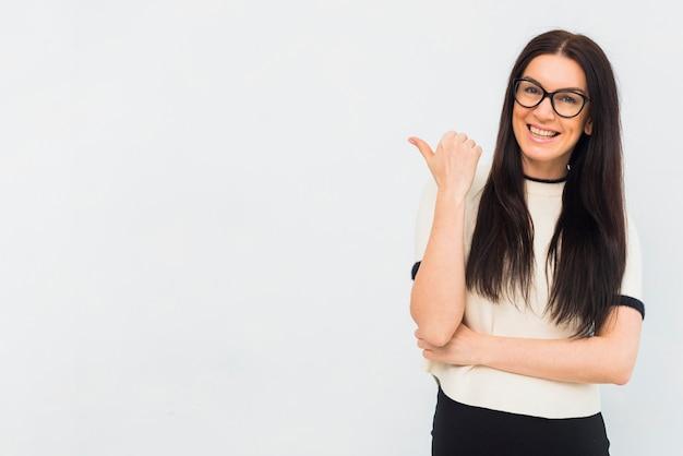 Vrouw in lichte kleren die weg met duim richten