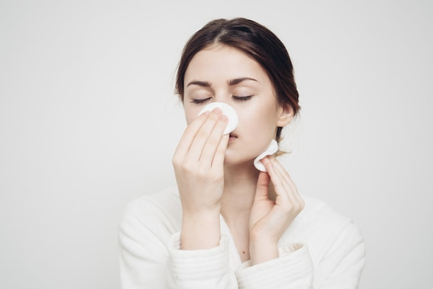 Vrouw in lichte kleren veegt haar gezicht af met een zachte spons schone huid cosmetologie.