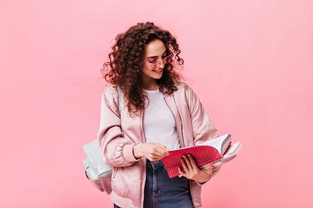 Vrouw in lichte outfit leest notities in notitieboekje op roze achtergrond