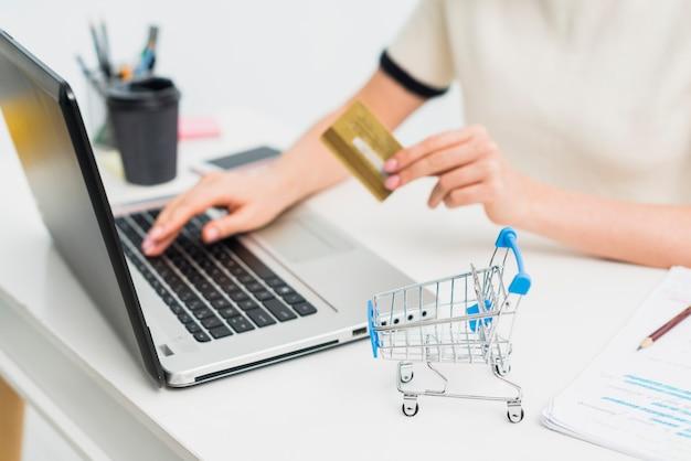 Vrouw in lichte zitting met creditcard bij lijst met laptop