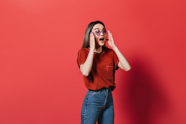 Vrouw in lila bril en rood t-shirt emotioneel poseren op geïsoleerde muur