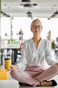 Vrouw in lotus houding op tafel op het werk, neem een pauze