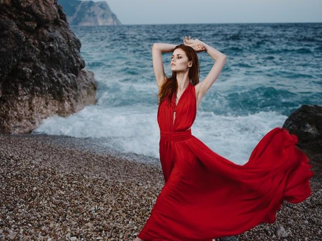 Vrouw in luxe rode jurk oceaan rotsachtige bergen
