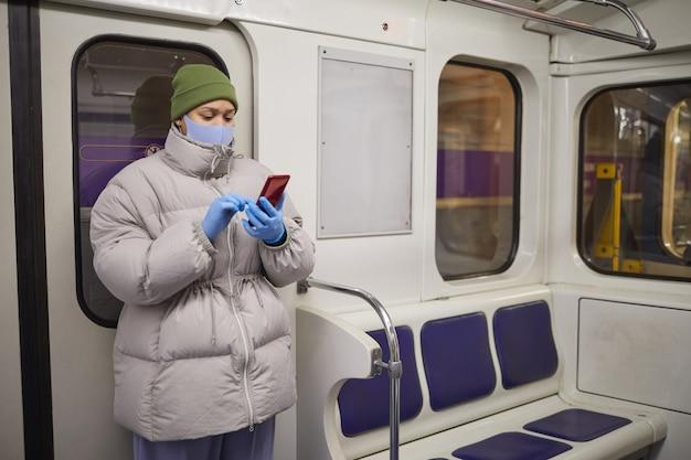 Vrouw in masker en in warme kleding een bericht typen op de mobiele telefoon terwijl ze in een trein in de metro staat