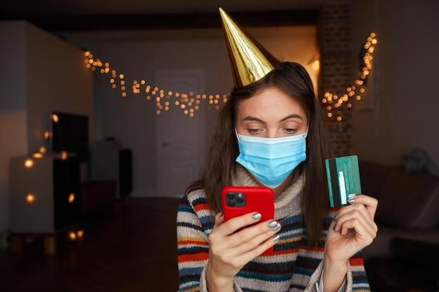Vrouw in masker en pet met behulp van creditcard en smartphone om geschenken te bestellen tijdens de viering van de vakantie thuis