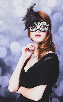 Vrouw in masker en zwarte jurk op grijs met bokeh