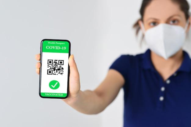 Vrouw in masker met smartphone met digitale groene pas