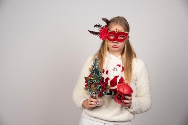 Vrouw in maskerademasker met cadeau en dennenboom.