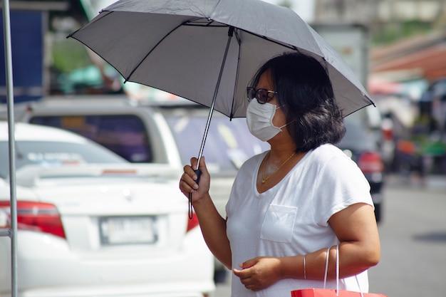 Vrouw in maskers voor bescherming tegen virussen en griep op drukke marktstraten