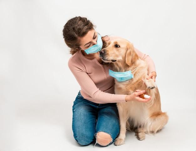 Vrouw in medisch beschermd gezichtsmasker desinfecteert hondenpoten met een ontsmettingsmiddel