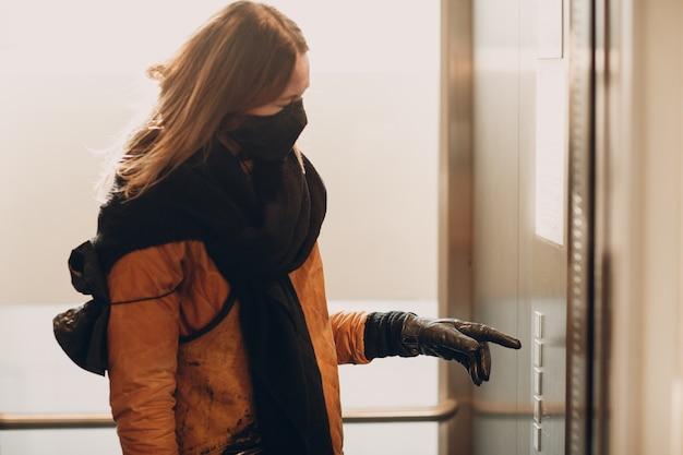 Vrouw in medisch gezichtsmasker met hand in handschoen wijsvinger op de knoplift tijdens coronavirus pandemie covid-19 quarantaineconcept