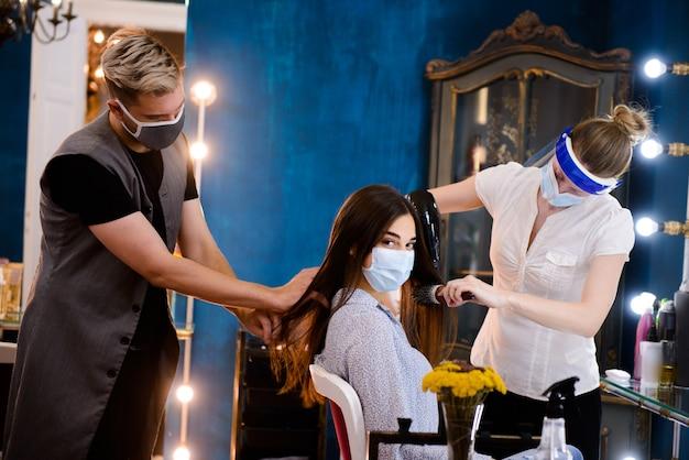 Vrouw in medisch masker bij de herenkapper