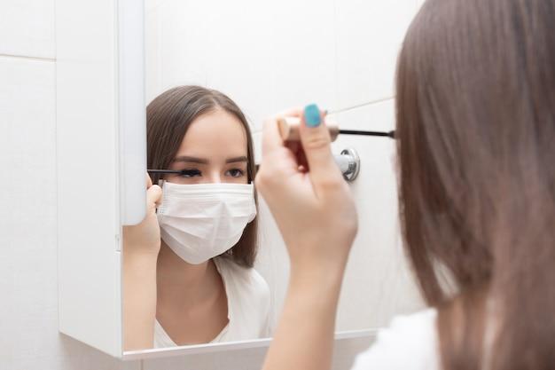 Vrouw in medisch masker doet make-up, mascara's ogen thuis in de badkamer