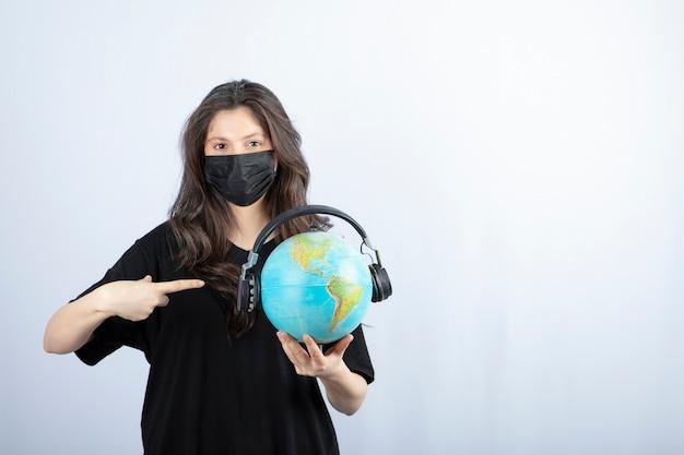 Vrouw in medisch masker houden en wijst naar wereldbol op witte tafel.