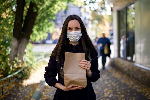 Vrouw in medisch masker met papieren zak in handen op straat, veilig winkelen concept, doneren