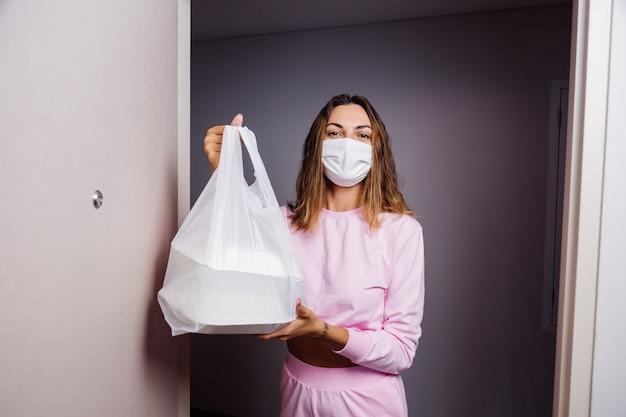 Vrouw in medisch wit gezichtsmasker krijgt plastic zak met voedsel van bezorger