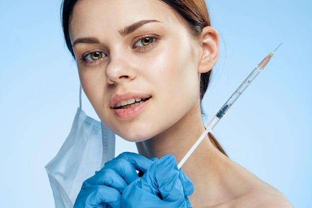 Vrouw in medische masker blauwe handschoen botox injectie collageen verjonging