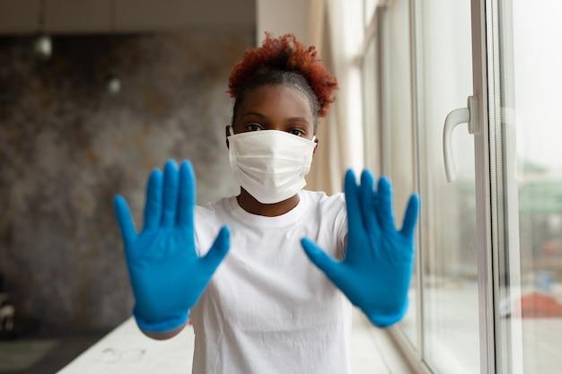 Vrouw in medische masker in de buurt van venster medische handschoenen met handgebaar dragen