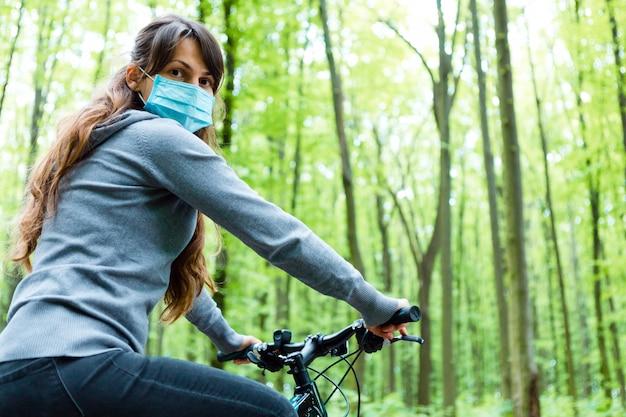 Vrouw in medische masker rijdt op een fiets in het park