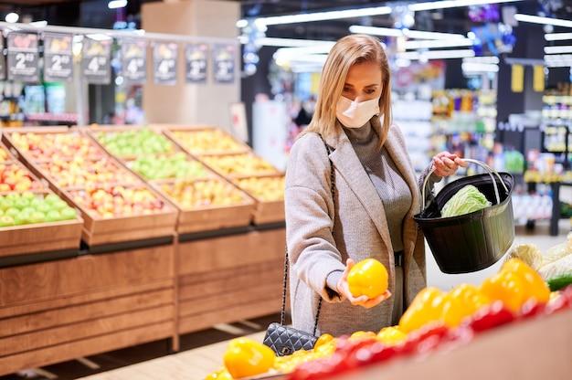 Vrouw in medische maskers winkelt in de supermarkt tijdens viruspandemie