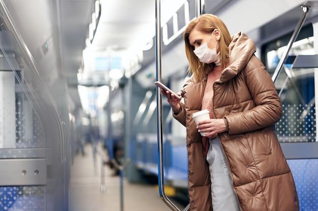 Vrouw in metrostation met beschermend chirurgisch hygiënemasker op gezicht voorkomt risico op coronavirus