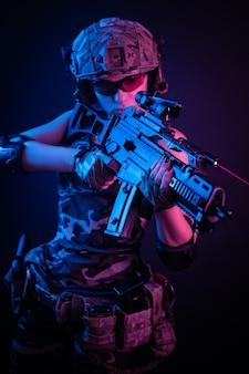 Vrouw in militaire overall airsoft poseren met een pistool in zijn handen op een donkere muur in de nevel in neonlicht