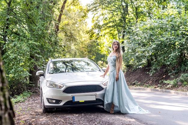 Vrouw in mint jurk staande rond de weg in de natuur