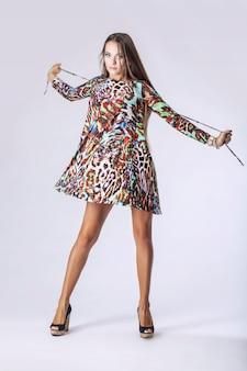 Vrouw in modieuze jurk in volle lengte in studio op lichte muur