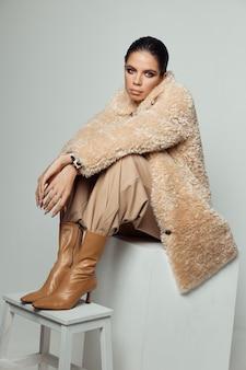 Vrouw in modieuze kleding bruine laarzen herfst stijl