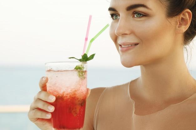 Vrouw in mooie jurk met glas cocktail