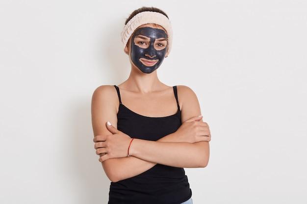 Vrouw in mouwloos t-shirt en haarband poseren met gezichtsmasker